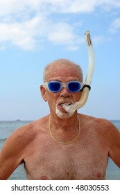 Man on a beach wearing blue dive goggles and snorkel