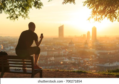 Man on a bench checking his smartphone and enjoying the summer sunrise over a city. Lyon, France.
