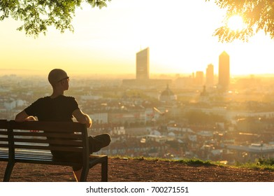 A man on a bench in a park, relaxing and  enjoying the summer sunrise over a city. Lyon, France.