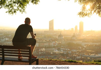 Man on a bench relaxing, checking his phone and enjoying the summer sunrise over a city. Lyon, France.