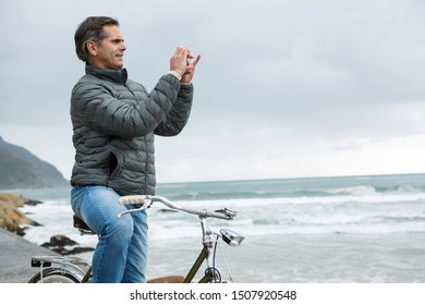 Man on bicycle taking picture on mobile phone on beach