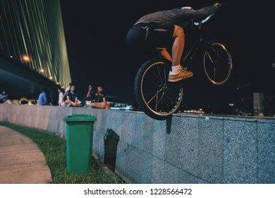 A man on a bicycle who is extremely jump with trials bike  sport at night time , An extreme man jumping on the trial bicycle