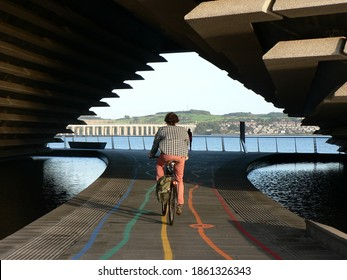 Man on a bike under the V and A museum in Dundee city centre with colourful lines and river in background