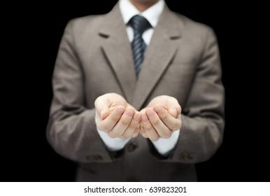 Man on black background with open hands. Holding, giving, showing concept.