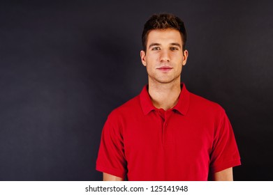 Man on black background in red shirt with smile