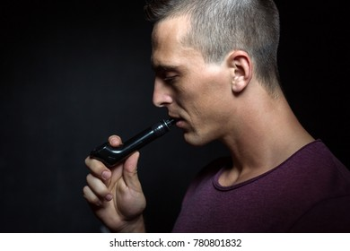 Man on black background vaping and releasing a cloud.