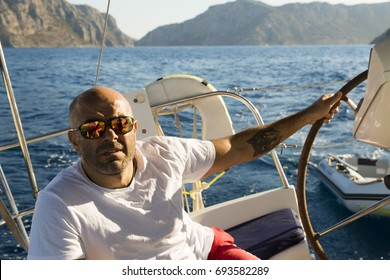 A man on the boat holding the wheel with white top and swimming short and sunglasses on