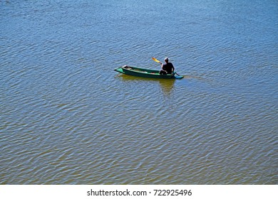 man on boat paddling in smooth water