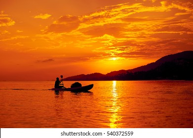 Man on a boat in the sea at beautiful sunset