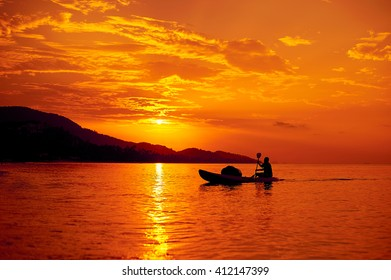 Man on a boat in the sea at sunset