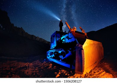 Man on bulldozer with head lamp under Milky Way view at night starry sky in the mountains
