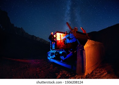 Man on bulldozer with red glowing cabin and Milky Way view at night starry sky in the mountains