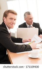 Man on business meeting. Cheerful young man in formalwear looking at camera while sitting at the business meeting