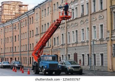 man on a car lift repairing a lantern