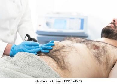Man on cavitation, ultrasound, lipolysis body treatment.