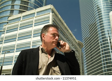A man on a cell phone with large glass covered high rise office building in the back ground.