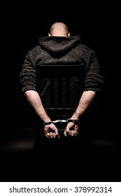 Man on chair in dark room sitting in handcuffs with head bowed