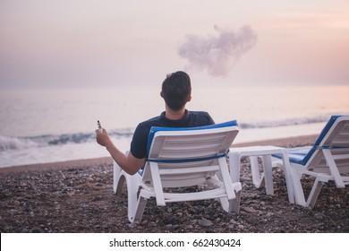 man on Chaise longue on sunset beach. Man facing a sea vaping e-cigarette