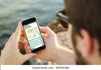 man on the coast with car sharing app on his smartphone . All screen graphics are made up.
