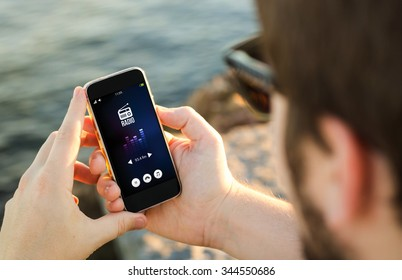 man on the coast with radio app on his smartphone . All screen graphics are made up.