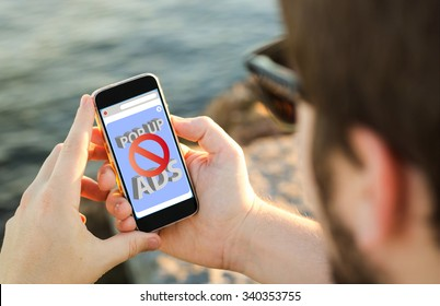 man on the coast using his smartphone with ads blocker. All screen graphics are made up.