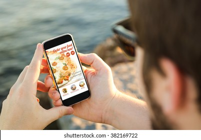 man on the coast using his smartphone to order pizza online. All screen graphics are made up.