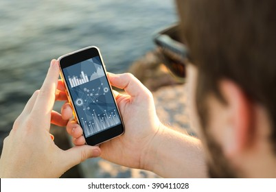 man on the coast using his smartphone checking stock market data. All screen graphics are made up.