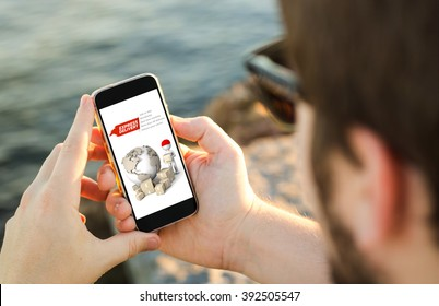 man on the coast using his smartphone showing express delivery website. All screen graphics are made up.