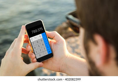 man on the coast using his smartphone with calculator app. All screen graphics are made up.