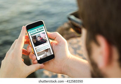 man on the coast using his smartphoneshowing social network. All screen graphics are made up.