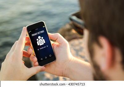 man on the coast using his smartphone setting privacy data. All screen graphics are made up.