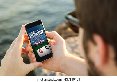 man on the coast using his smartphone to play poker. All screen graphics are made up.