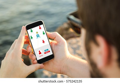man on the coast using his smartphone to split expenses between friends with app. All screen graphics are made up.