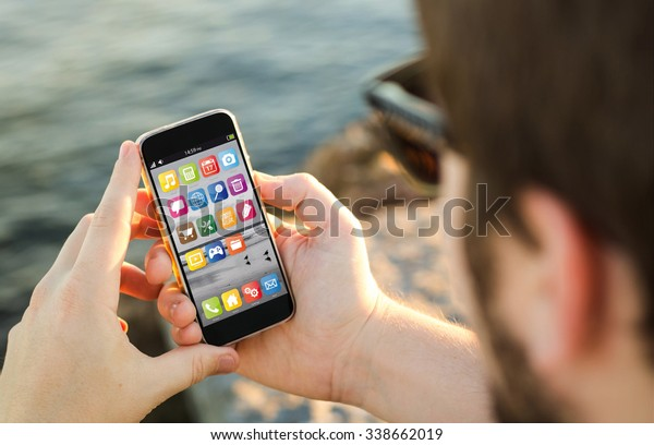 man on the coast using his smartphone. All screen graphics are made up.
