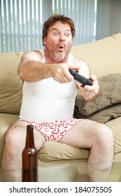 Man on the couch playing a video game in his underwear. Beer bottle in foreground.