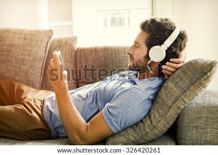 Man on couch watches a movie on mobile phone