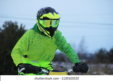 A man on a cross-motorcycle trains in the winter in the snow.