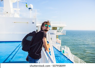 Man on cruise at railing on Liner. Touris on ferry boat enjoying the view.