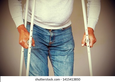 Man on crutches on a gray background. Close-up a elderly man walking with crutches.