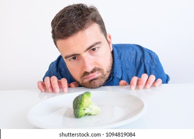 Man on diet feeling hungry and bored by vegetable meal
