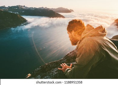 Man on the edge cliff above sea gaze into abyss lying down traveling in mountains adventure lifestyle extreme vacations
