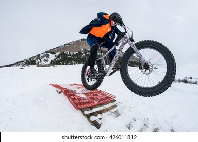 Man on fat bike going off jump in snow.