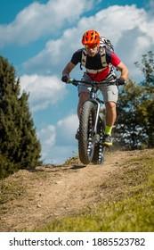 Mann auf einem fetten Fahrrad stürmen oder bergab fahren. Professionelles Fahrrad auf einem Weg mit einem dicken Fahrrad.