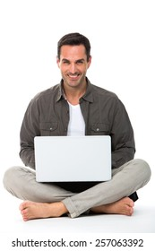 Man on the floor, smiling at camera and working with his laptop
