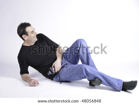 Man on the floor of studio laughing.He is wearing t-shirt and blue jeans with no shoes and holding a light meter.