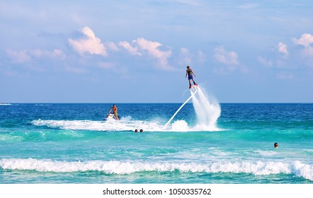 Man on flyboard KOH SAMUI, THAILAND-JANUARY 5, 2015: Young man having fun on water jet boots flyboard