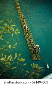 Man on green bamboo raft rows down river