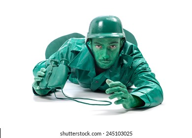 Man on a green toy soldier costume, crawling with binocolous isolated on white background.
