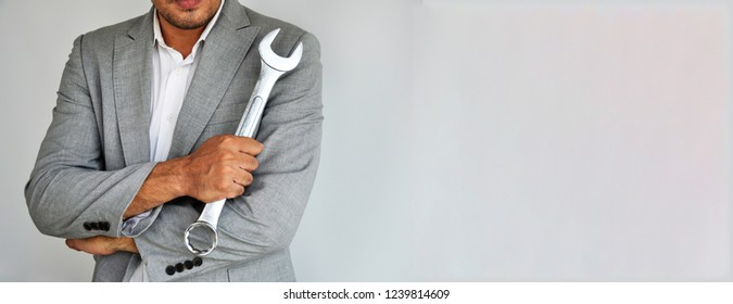 Man on grey suit. Man holding wrench on grey background with copy space.