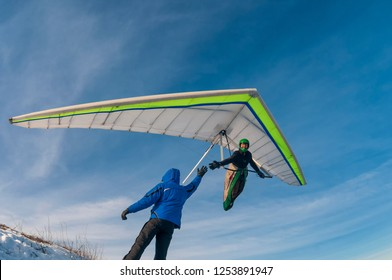 Man on the ground and hang glider pilot in the air shake hands. Inspiration to flying and lifetime achievement.
